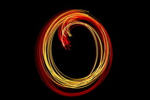 Long Exposure Photograph Of Neon Colour In An Abstract Circle Swirl, Parallel Lines Pattern Against A Black Background. Light Painting Photography.