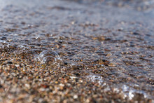 Closeup Of Tiny Bubbles Created By Wave Rolling On The Beach