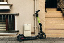 An Electric Scooter Is Parked At The Entrance To A Residential Building