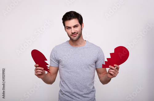 Charming handsome man with a red broken heart on a white background Fototapet