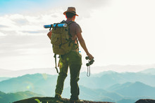 The Hiker With A Backpack Stood On The Rock After Examining The Map To Find A Path In A Beautiful Mountain Landscape.