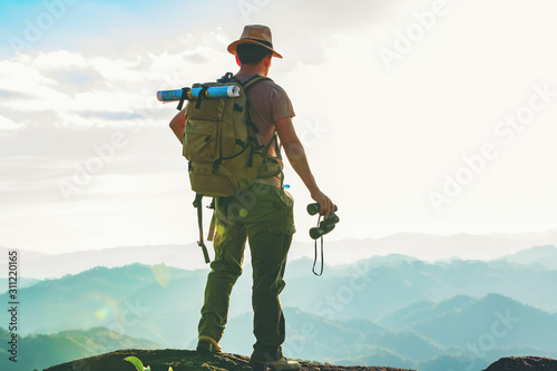 Fotografie, Obraz The hiker with a backpack stood on the rock after examining the map to find a path in a beautiful mountain landscape
