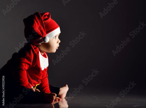 Amazed baby boy toddler in red santa claus costume is sitting on ice on dark loo Wallpaper Mural