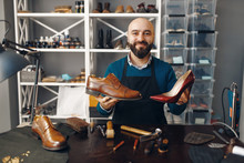 Bootmaker Shows Repaired Shoes...