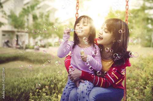 Papel de parede  Mother holding her daughter happily while swinging