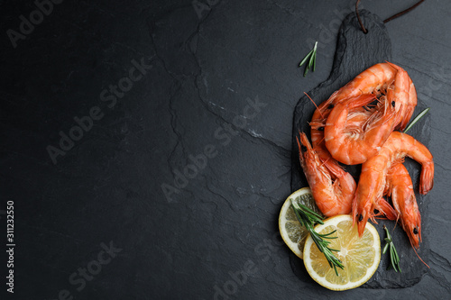 Fotografiet Delicious cooked shrimps with lemon and rosemary on black table, flat lay