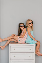 Two Stylish Little Girls In Colorful Dresses And Sunglasses With Emotional Faces Siiting On Dresser Over Gray Wall On Background.