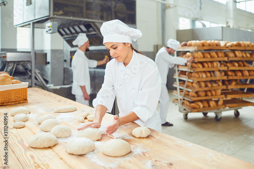 Tableau sur Toile A woman baker smileswith colleagues at a bakery.