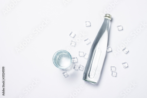 Fotografía  Bottle of pure crystal water with ice cubes and glass on a white background under sunlight