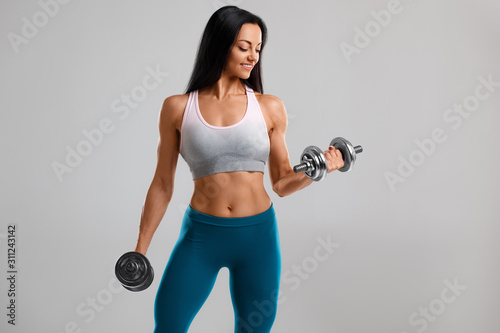 Valokuva Fitness woman doing exercise for biceps on gray background