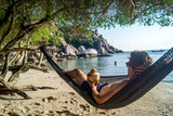 young man relaxing in hammock on the beach