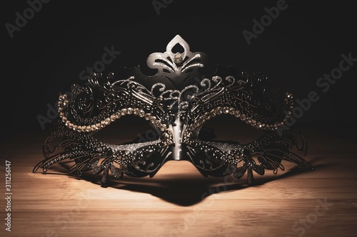 Fotografie, Obraz  A portrait of a traditional venetian mask on a wooden surface appearing mysteriously out of the darkness