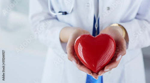 Cuadros en Lienzo Female doctor with stethoscope holding heart, on light background