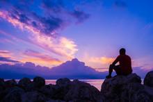 Young Man Sitting On Sea Rocks...