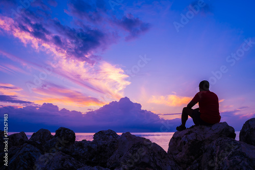 Young man sitting on sea rocks by the beach thinking, contemplating, determining the way forward. Life changing decisions. Priority decision making. Freedom to choose. Passing time as the sun sets. - 311267983