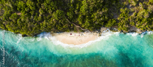 View from above, stunning aerial view of some tourists sunbathing on a beautiful beach bathed by a turquoise rough sea during sunset, Green Bowl Beach, South Bali, Indonesia Canvas