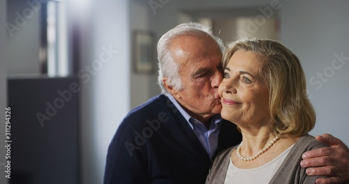 Carta da parati  Close up of a lovely senior husband is giving a kiss to his wife as a sign of forever love at home
