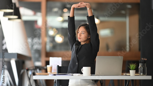 Obraz na płótnie Businesswoman relaxing at comfortable in office hands behind head, happy woman resting in office satisfied after work