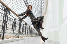 Conceptual Posing. European Beautiful Girl With Long Red Hair In A Black Dress With A Floral Print And Batilions Leans On Railing In A Strange Position