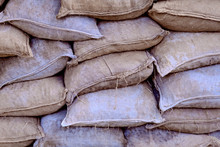 Background Of Retro Sacking Background Of Full Burlap Gray Bags. Protective Wall Of Sandbags.