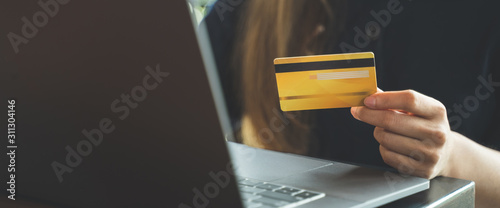 Obraz Close up hand of woman holding credit card shopping on website. - fototapety do salonu