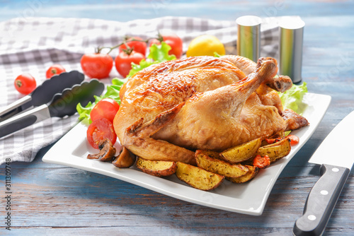 Fototapeta Plate with baked chicken and potato on table obraz
