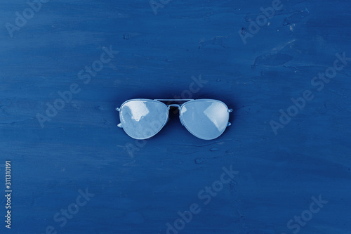 Blue aviator glasses on classic blue background, top view Wallpaper Mural