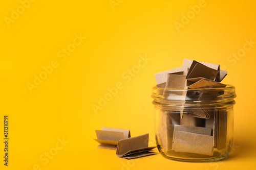 Fotografia  Glass jar full of brown paper sheets on yellow background, space for text