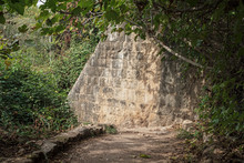 Section Of The Ancient Stone Wall Of The Historic Hydroelectric Power Plant On The Hermon Stream Trail In Israel Surrounded By Dense Semitropical Vegetation