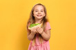 Cute little girl with tasty sandwich on yellow background