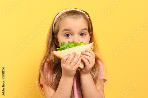 Canvastavla Cute little girl eating tasty sandwich on yellow background