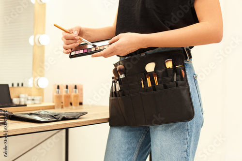 Obraz na plátne Professional makeup artist with eyeshadow palette and belt organizer full of too