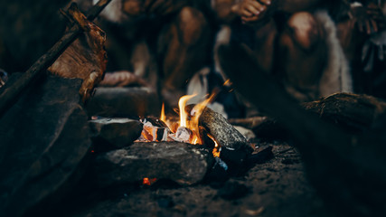 Close-up of Tribe Prehistoric Hunter-Gatherers Trying to Get Warm at the Bonfire, Holding Hands over Fire, Cooking Food. Neanderthal or Homo Sapiens Family Live in Cave at Night.