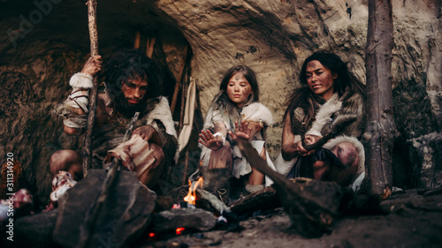 Fotografie, Tablou Tribe of Prehistoric PrimitiveHunter-Gatherers Wearing Animal Skins Live in a Cave at Night
