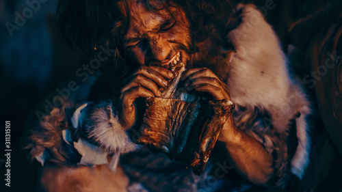 Slika na platnu Close-up Portrait of Tribe Leader Wearing Animal Skin Eating in a Dark Scary Cave at Night