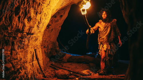 Fotografiet Primeval Caveman Wearing Animal Skin Exploring Cave At Night, Holding Torch with Fire Looking at Drawings on the Walls at Night