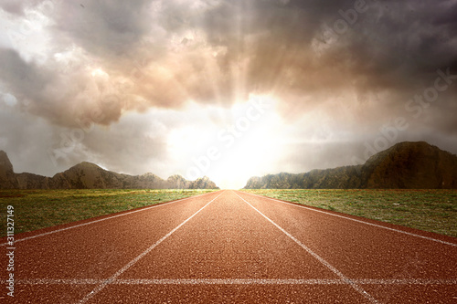 Fototapeta Running track with green grass and mountain view