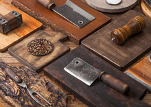 Different Sizes And Shapes Kitchen Chopping Boards On Wooden Background With Meat Hatchets, Fork And Knife And Other Utensils. Top View