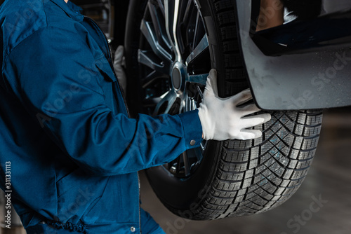 cropped view of mechanic installing new tire on car Canvas-taulu
