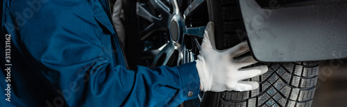 Fototapeta cropped view of mechanic installing wheel on car in workshop, panoramic shot obraz