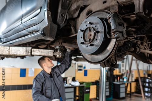 Fototapeta selective focus of assembled disc brakes near young mechanic examining raised car obraz