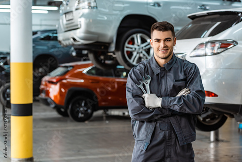 smiling mechanic looking at camera while standing with crossed arms and holding wrenches