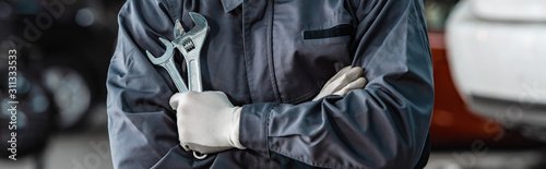 Fotografia  cropped view of mechanic holding wrenches while standing with crossed arms