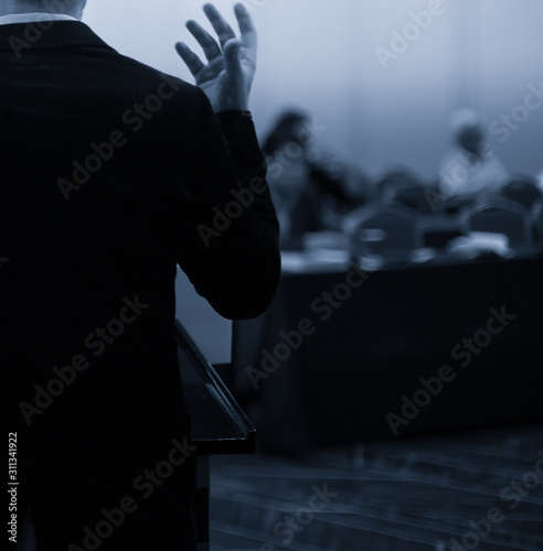 Fototapety, obrazy: Presenter at corporate conference giving speech. Speaker giving lecture to business audience in seminar. Executive manager leading discussion in hall during company training event.