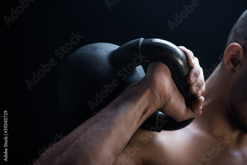 Fotografia  cropped view of muscular bodybuilder excising with kettlebell isolated on black