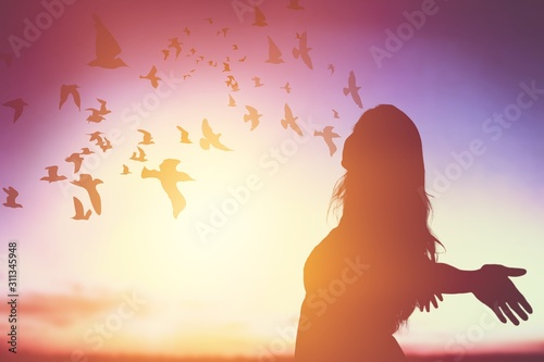 Fotografie, Tablou  Silhouette man rising hands on sunset sky, Human Freedom concept