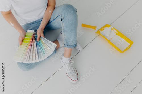 Obraz Faceless woman in jeans holds color samples, chooes best tone for refurbishment walls, sits on white floor, uses tray and paint roller for house remodeling. Home makeover and renovation concept - fototapety do salonu