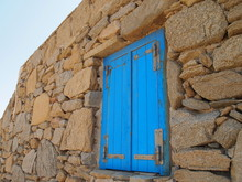 Blue Wooden Window In The Wall Of An Old Stone House On The Island Of Mykonos In Greece