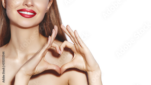 Romantic young Woman making Heart Shape with her Fingers. Love and Valentines Day Symbol. Fashion girl with Happy Smile - fototapety na wymiar