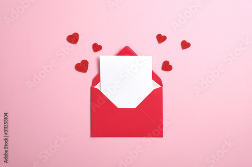 Fotografie, Obraz Red paper envelope with blank white note mockup inside and Valentines hearts on pink background